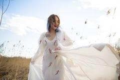 Portrait de jeune belle fille dans la robe blanche dans le domaine de bl?, marche, insouciante Appr?cier le beau jour ensoleill? photos libres de droits