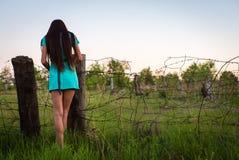 Portrait de jeune belle fille dans une robe de turquoise près de barbelé en été extérieur photographie stock
