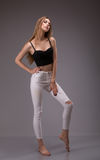 Portrait de jeune, blonde, caucasienne femme attirante dans le dessus noir de culture et de la pose blanche de pantalon Projectil photos libres de droits
