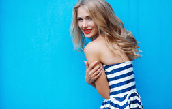 Portrait de jeune blonde sur un fond bleu image libre de droits