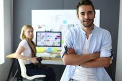 Portrait de jeune concepteur devant l'ordinateur portable et l'ordinateur tout en travaillant Assistant employant son mobile au f photos stock