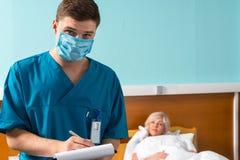 Portrait de jeune docteur dans l'uniforme portant un masque faisant un certain n Images stock