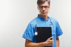 Portrait de jeune docteur heureux à la clinique, regardant l'appareil-photo Photographie stock