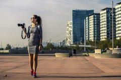 Portrait de jeune et attirant photographe dans la robe grise et des espadrilles lumineuses Photos stock