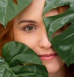 Portrait de jeune et belle femme dans des feuilles tropicales photo stock