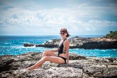 Portrait de jeune et sexy femme sur les roches près de l'océan sauvage Tempête, vagues énormes venant et éclaboussant tropical Photographie stock