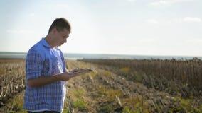 Portrait de jeune exploitant agricole avec la position de tablette dans le domaine Agriculteurs de concept, nourriture, bio produ banque de vidéos
