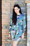Portrait de jeune femme à la mode se tenant près d'un mur en pierre dans le col Image stock