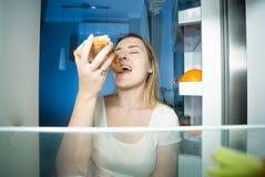 Portrait de jeune femme affamée se tenant au réfrigérateur ouvert la nuit et mangeant de la pizza Photo stock