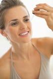 Portrait de jeune femme appliquant l'élixir cosmétique Image libre de droits