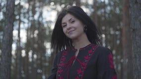 Portrait de jeune femme attirante attachant la dentelle sur un noir et une position rouge de robe sous les arbres dans la forêt d banque de vidéos