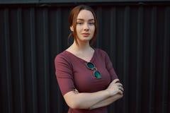 Portrait de jeune femme attirante posant contre le mur foncé image stock