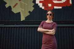 Portrait de jeune femme attirante posant contre le mur foncé images libres de droits
