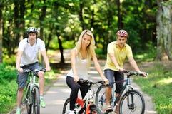 Portrait de jeune femme attirante sur la bicyclette et deux hommes dans bleu Photos stock