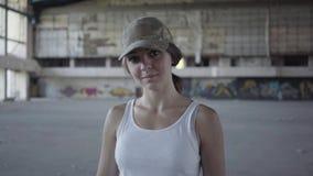 Portrait de jeune femme attirante touchant son chapeau militaire sur sa tête et inclinant la tête le regard dans la caméra se ten clips vidéos