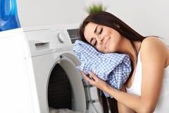 Portrait de jeune femme au foyer avec la blanchisserie à côté de la machine à laver images libres de droits