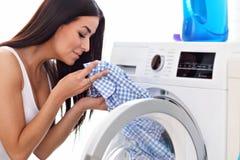 Portrait de jeune femme au foyer avec la blanchisserie à côté de la machine à laver photo stock