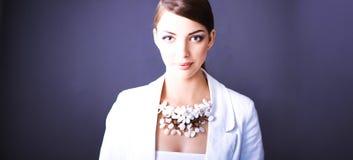 Portrait de jeune femme avec des perles, se tenant sur le fond gris Photographie stock libre de droits