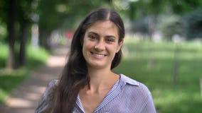 Portrait de jeune femme avec du charme regardant et souriant avec des dents l'appareil-photo, se tenant en parc, journée, dehors banque de vidéos