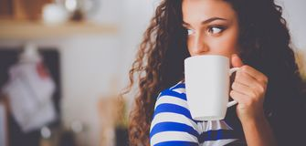 Portrait de jeune femme avec la tasse sur le fond d'intérieur de cuisine photo libre de droits