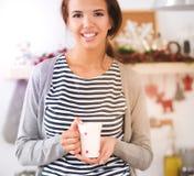 Portrait de jeune femme avec la tasse sur le fond d'intérieur de cuisine photographie stock