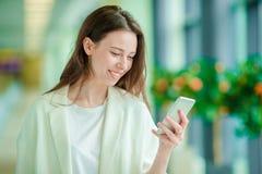 Portrait de jeune femme avec le smartphone dans l'aéroport international Passager de ligne aérienne dans un salon d'aéroport atte Images stock
