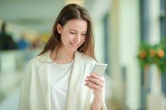 Portrait de jeune femme avec le smartphone dans l'aéroport international Passager de ligne aérienne dans un salon d'aéroport atte Image libre de droits
