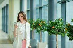Portrait de jeune femme avec le smartphone dans l'aéroport international Passager de ligne aérienne dans un salon d'aéroport atte Images libres de droits