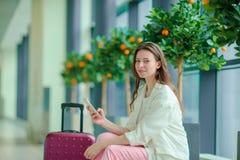 Portrait de jeune femme avec le smartphone dans l'aéroport international Passager de ligne aérienne dans un salon d'aéroport atte Photos stock