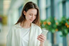 Portrait de jeune femme avec le smartphone dans l'aéroport international Passager de ligne aérienne dans un salon d'aéroport atte Photo stock