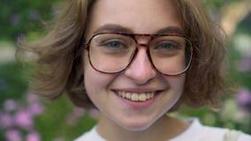 Portrait de jeune femme avec les cheveux courts mettant sur des verres et le sourire banque de vidéos