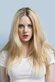 Portrait de jeune femme blonde attirante avec les lèvres rouges sur le fond bleu-clair Photographie stock libre de droits