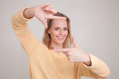 Portrait de jeune femme blonde avec l'expression heureuse gaie sur son visage, avec bonne humeur, faisant la place avec ses doigt image libre de droits