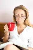 Portrait de jeune femme blonde de belle fille avec du charme mignonne en verres tenant le livre de lecture disponible de tasse rou Image stock