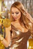 Portrait de jeune femme blonde entre les ballons et le ruban d'or photo libre de droits