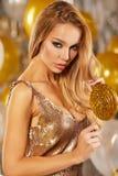Portrait de jeune femme blonde entre les ballons et le ruban d'or image libre de droits
