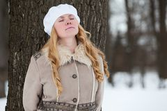 Portrait de jeune femme caucasienne dans le manteau se penchant au tronc d'arbre avec les yeux fermés en parc d'hiver Photographie stock libre de droits