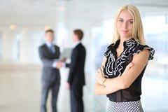 Portrait de jeune femme d'affaires dans le bureau avec des collègues à l'arrière-plan Images libres de droits