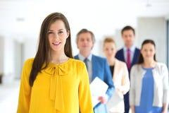 Portrait de jeune femme d'affaires de sourire avec l'équipe à l'arrière-plan au bureau Image libre de droits