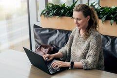 Portrait de jeune femme d'affaires en verres à la mode se reposant en café, travaillant à l'ordinateur portable Le Blogger commun photos libres de droits