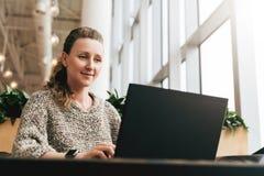 Portrait de jeune femme d'affaires en verres à la mode se reposant en café, travaillant à l'ordinateur portable Le Blogger commun images libres de droits