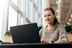 Portrait de jeune femme d'affaires en verres à la mode se reposant en café, travaillant à l'ordinateur portable Le Blogger commun image libre de droits