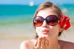 Portrait de jeune femme dans des lunettes de soleil soufflant Photo libre de droits