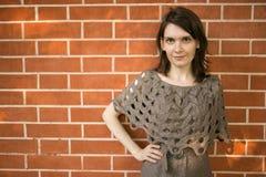Portrait de jeune femme dans la robe de knit contre l'espace rouge brique de fond et de copie Photographie stock