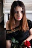 Portrait de jeune femme dans la robe de soirée avec une rose rouge dans des ses mains Image libre de droits