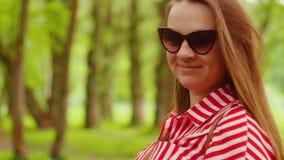 Portrait de jeune femme dans la robe rouge en été Jeune femme heureuse souriant ? l'appareil-photo Fermez-vous vers le haut du ti banque de vidéos