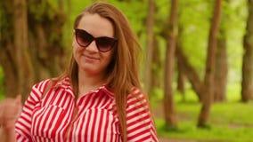 Portrait de jeune femme dans la robe rouge en été Jeune femme heureuse souriant ? l'appareil-photo banque de vidéos