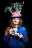 Portrait de jeune femme dans la similitude du chapelier avec la tasse Photographie stock libre de droits