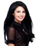 Portrait de jeune femme de sourire avec de longs cheveux bruns. Image stock