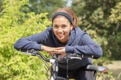 Portrait de jeune femme de sourire s'exerçant avec la bicyclette, extérieur photographie stock